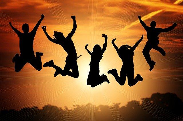 夕陽の中ジャンプする五人の若者