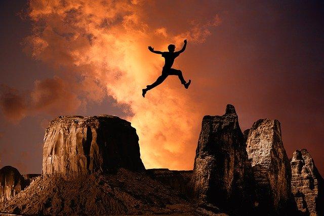 岩から岩へ飛んでいる青年