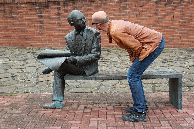 銅像に話しかけるおじさん