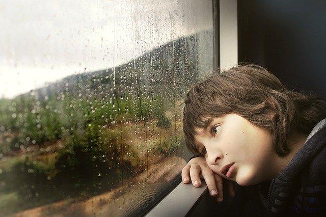 窓の外を見つめる少年