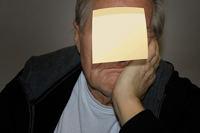 額にポストイットを貼って頬杖をついている男性